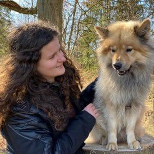 Alena mit ihrem Hund, der auf einem Baumstumpf sitzt