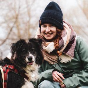 Rebecca aus dem Patenteam mit ihrem Hund schauen in die Kamera